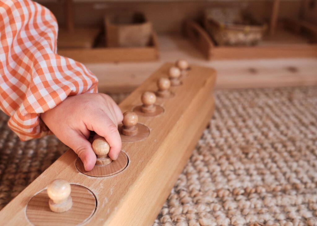 una nina con cilindors de boton en el ambiente preparado de un aula montessori